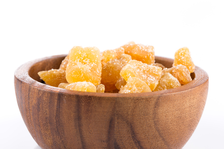 heap of sweat Candied ginger isolated on white background in wooden bowl 版權商用圖片