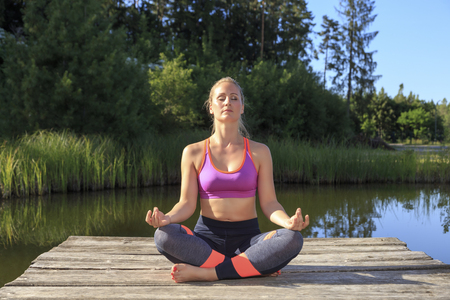 turner: A sporty woman doing yoga and stretching exercises Stock Photo