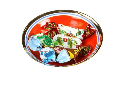 set of candies in sweet wrapper on red saucer photo
