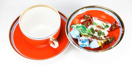 caramel and chocolate candy on red saucer with cup photo