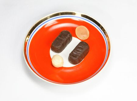 caramel and chocolate candy on red saucer photo