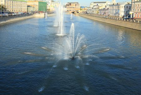 fountain on river in city at evening photo