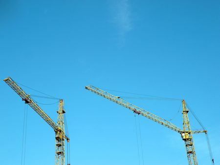 two crane towers on sky background at day photo