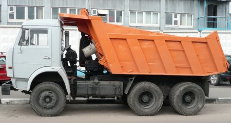 dumper: orange truck on asphalt road   Stock Photo