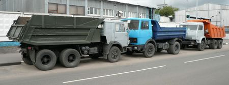 grey, blue and orange trucks on road photo