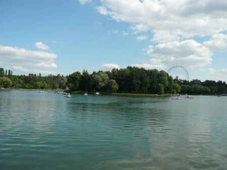 Ferris wheel and lake in park at dry sunny summer day photo