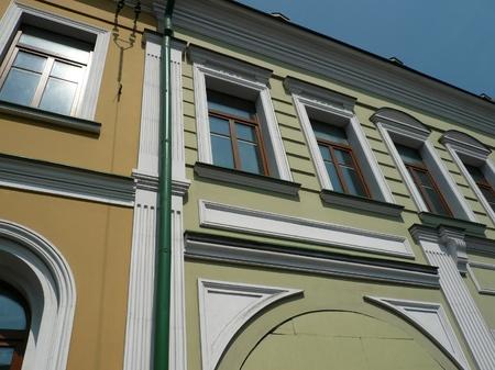 waterspout: giallo antico edificio con tubo a tempesta verde al giorno Archivio Fotografico