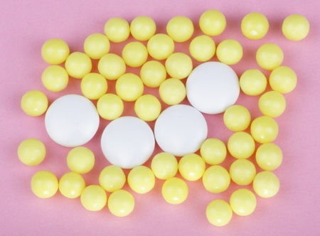 yellow vitamins on pink background  photo
