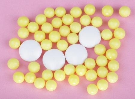 yellow vitamins on pink background  photo