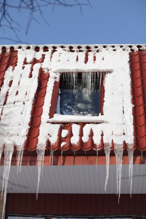 icicles on building roof at sunny winter day photo