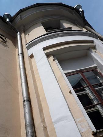 waterspout: vecchio edificio giallo con storm-down pipe al giorno