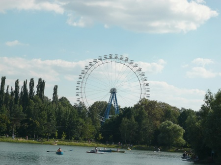 Ferris wheel and lake in park at sunny day photo