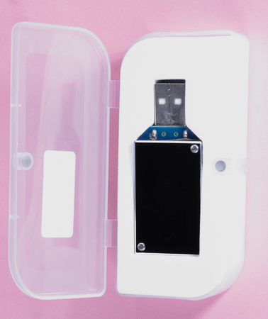 electronic device in plastic case on pink background at day Stockfoto
