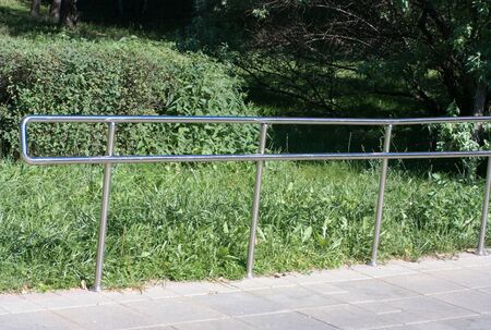 metal fence in park at dry sunny summer day Stock Photo