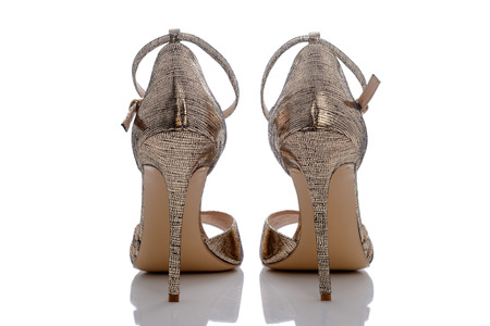 clasp feet: designer and firm sandals of golden color with shine Stock Photo