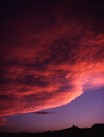 Blanket Of Clouds Moves Towards A Mountain Range At Sunset LANG_EVOIMAGES