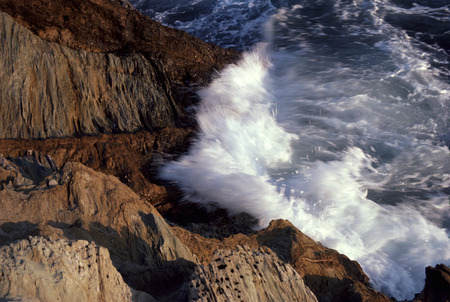 Waves Hit Against A Rocky Coastline Shore
