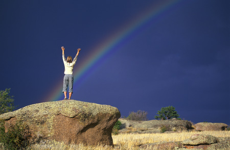 Woman Raising Both Arms With Rainbow Over The Sky In Background