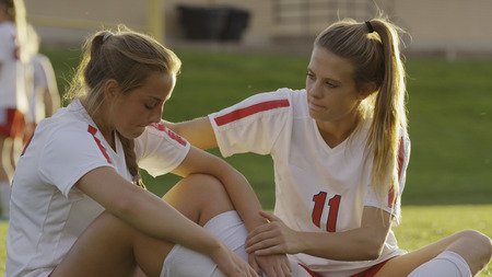 Serious Soccer Athlete Comforting Teammate After Losing Game Outdoors LANG_EVOIMAGES