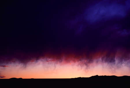 A Storm Cloud Hovers Above A Long Hillside During Sunset