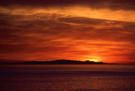 A Horizontal Photograph Of A Tropical Sunset Over An Island Bay LANG_EVOIMAGES