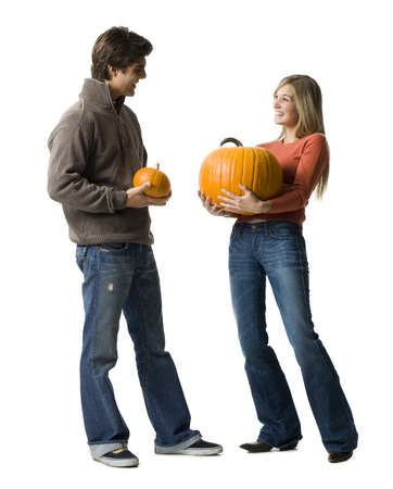 Young Couple Standing Face To Face Holding Pumpkins