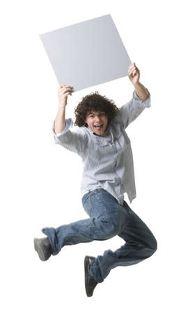 Portrait Of A Teenage Boy Holding A Blank Sign And Jumping In Mid-Air