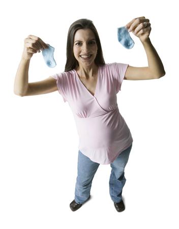 Vista de alto ángulo de una mujer embarazada sosteniendo calcetines para bebés