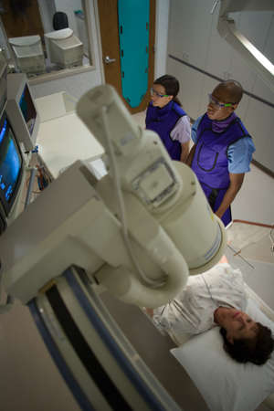 High Angle View Of Two Doctors Examining A Patient