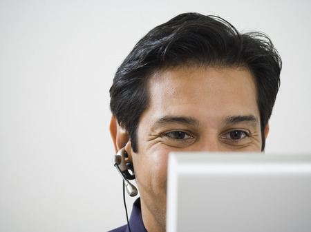 handsfree telephones: Close-Up Of A Mature Man In Front Of A Computer