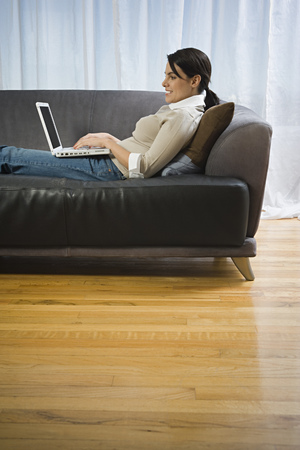 Profile Of A Mid Adult Woman Reclining On A Couch Working On A Laptop