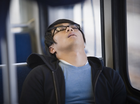Close-Up Of A Young Man Sleeping On A Commuter Train