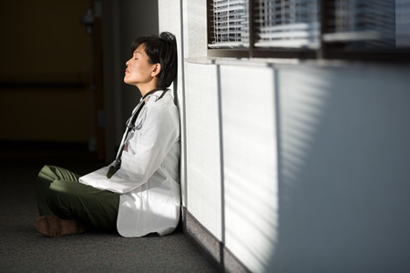 Profile Of A Female Doctor Sitting On The Floor With Her Eyes Closed