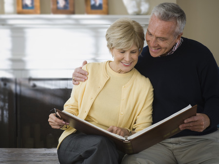 An Elderly Couple Looking At A Photo Album