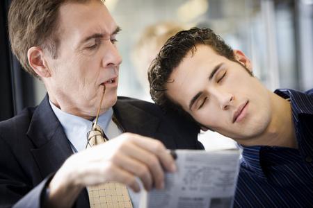 Close-Up Of A Young Man Asleep On A Mature ManS Shoulder