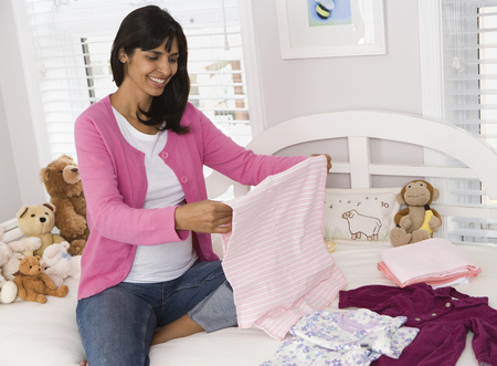 Pregnant Woman Folding Clothes