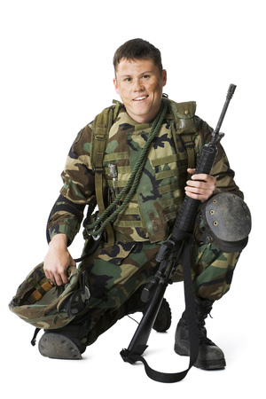 Portrait Of A Soldier Crouching And Holding A Rifle And A Helmet LANG_EVOIMAGES