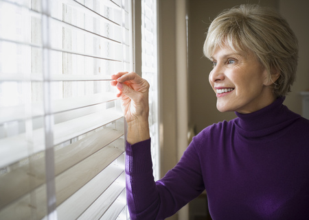 Mature Woman Looking Through Blinds Of A Window