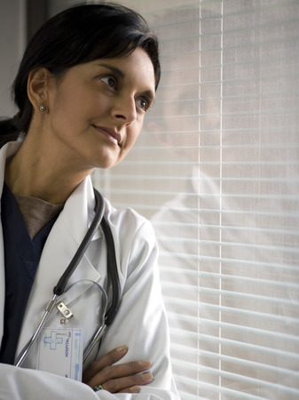 Close-Up Of A Female Doctor Leaning Against A Window With Her Arms Crossed