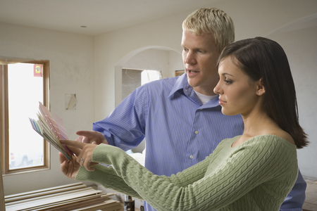 decorating: Young White Couple Looking At A Paint Color Swatch LANG_EVOIMAGES