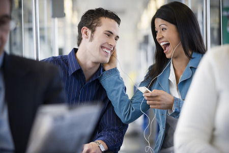 Woman Sharing Her Mp3 Player With A Young Man On A Commuter Train LANG_EVOIMAGES