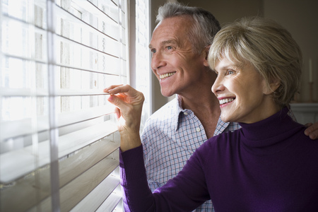 Mature Couple Looking Through Window Blinds