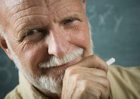 the elderly tutor: Portrait Of A Senior Male Professor Holding A Chalk LANG_EVOIMAGES