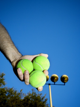 offset up: Low Angle View Of A Person Holding Three Tennis Balls