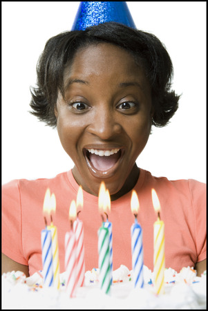 Close-Up Of A Young Woman Smiling In Front Of A Birthday Cake LANG_EVOIMAGES