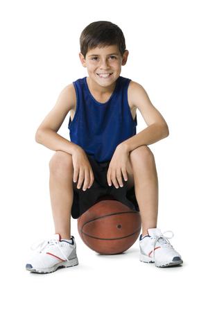 Portrait Of A Boy Sitting On A Basketball
