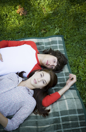 High Angle View Of A Teenage Couple Lying In The Park