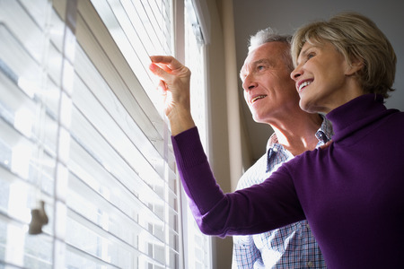 Low Angle View Of A Mature Couple Looking Through Blinds Of A Window