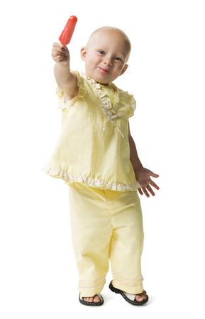 calvicie: Retrato de una niña sosteniendo un helado y sonriente LANG_EVOIMAGES