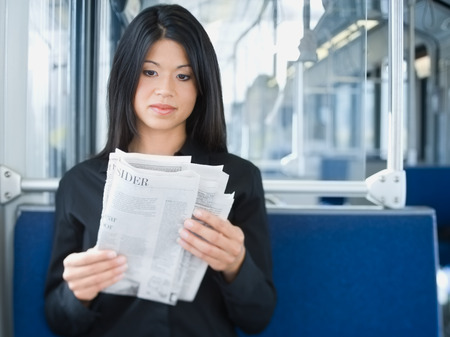 Close-Up Of A Woman Reading A Newspaper On A Commuter Train LANG_EVOIMAGES